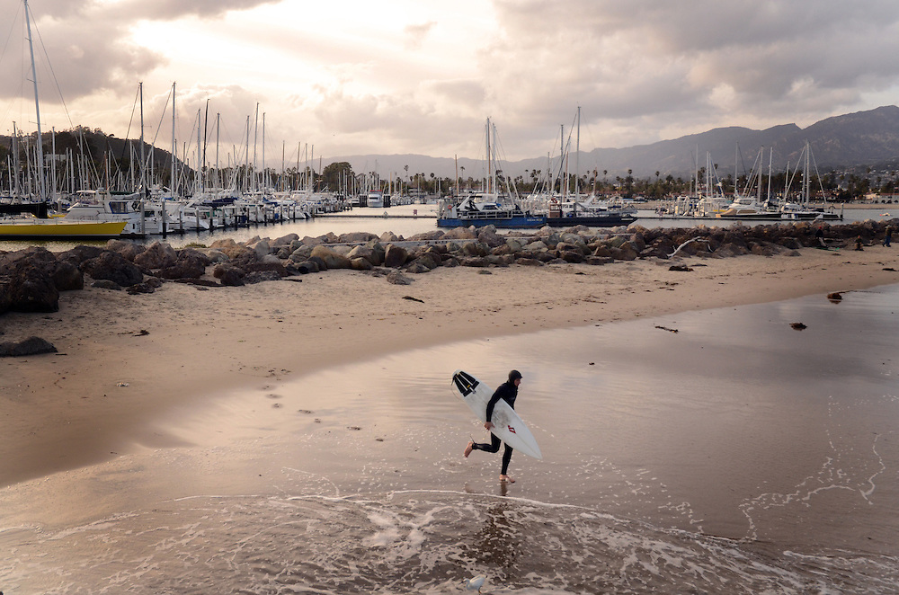 San Diego Fitness Photographer: Male surfer runs out into the ocean from Santa Barbara Harbor, Santa Barbara, CA. USA