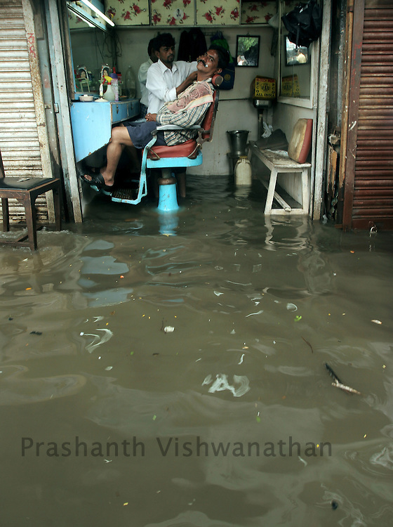 A barber attends to customer in his flooded shop on a road in Mumbai, India, on Sunday, June 24, 2007. Photographer: Prashanth Vishwanathan/Atlas Press