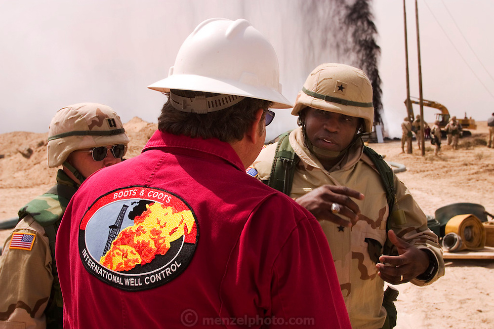 General Crear of the Army Corps of Engineers talks with Larry Flak of Boots and Coots near a burning oil well just extinguished by Boots and Coots in Iraq's Rumaila Oil Field. Flak headed the 1991 firefighting effort in Kuwait that extinguished more than 700 oil well fires placed by retreating Iraqi troops. The Rumaila field is one of Iraq's biggest oil fields with five billion barrels in reserve. Rumaila is also spelled Rumeilah.