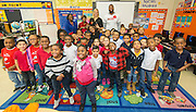 Kami Graig and Wade Smith pose for a photograph with students during a Touchdown Houston Read On literacy program at Ross Elementary School, December 2, 2016.