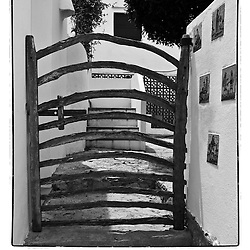 A black and white print of a wooden gate that leads to a small house on Menorca.