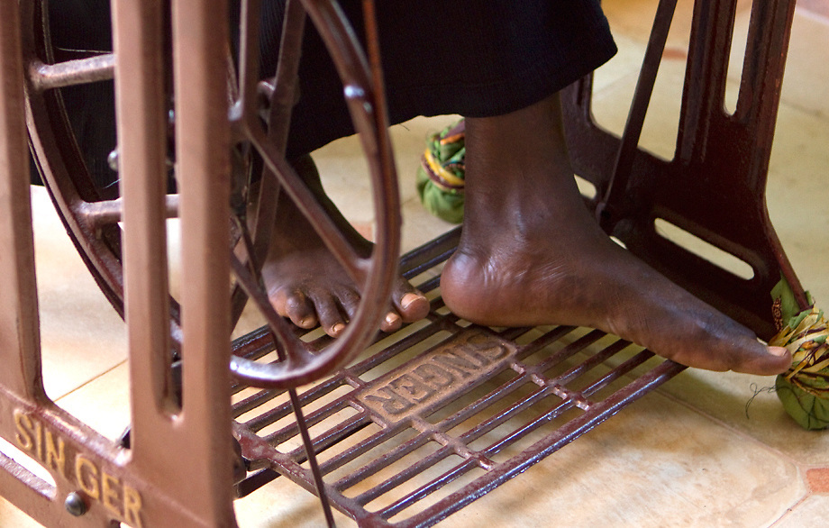 Bare feet on treadle sewing machine.  Wrap Up Africa, Kampala, Uganda