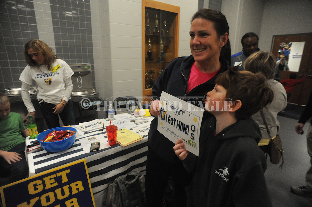 Renee Joyce (left) and her son Colby hold up a replica of a car tag after signing up for an Oxford High School license plate, at Oxford High School in Oxford, Miss. on Friday, February 6, 2015.