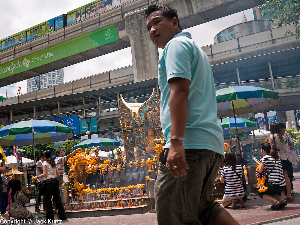 11 JULY 2011 - BANGKOK, THAILAND:   A man walks past the Erawan Shrine in Bangkok. The Erawan Shrine (in Thai San Phra Phrom) is a Hindu shrine in Bangkok, Thailand that houses a statue of Phra Phrom, the Thai representation of the Hindu creation god Brahma. A popular tourist attraction, it often features performances by resident Thai dance troupes, who are hired by worshippers in return for seeing their prayers at the shrine answered. On 21 March 2006, a man vandalised the shrine and was subsequently killed by bystanders. The shrine is located by the Grand Hyatt Erawan Hotel, at the Ratchaprasong intersection of Ratchadamri Road in Pathum Wan district, Bangkok, Thailand. It is near the Bangkok Skytrain's Chitlom Station, which has an elevated walkway overlooking the shrine. The area has many shopping malls nearby, including Gaysorn, CentralWorld and Amarin Plaza. The Erawan Shrine was built in 1956 as part of the government-owned Erawan Hotel to eliminate the bad karma believed caused by laying the foundations on the wrong date..The hotel's construction was delayed by a series of mishaps, including cost overruns, injuries to laborers, and the loss of a shipload of Italian marble intended for the building. Furthermore, the Ratchaprasong Intersection had once been used to put criminals on public display. An astrologer advised building the shrine to counter the negative influences. The Brahma statue was designed and built by the Department of Fine Arts and enshrined on 9 November 1956. The hotel's construction thereafter proceeded without further incident. In 1987, the hotel was demolished and the site used for the Grand Hyatt Erawan Hotel.     PHOTO BY JACK KURTZ