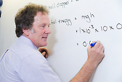 Secondary School Science teacher writing on a whiteboard to explain to students the formula of a kinetic energy experiment on why and how things move,