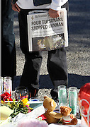 A man holds a local newspaper at the memorial outside the hospital where shooting victims are recovering in Tucson, Arizona January 11, 2011. REUTERS/Rick Wilking (UNITED STATES)