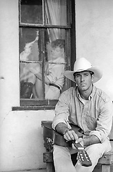 cowboy sitting on a bench while a woman looks on through a window