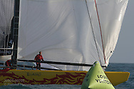 China Team crew begins pulling in spinnaker as bow passes green buoy marking finish of America's Cup fleet race; Valencia, Spain.