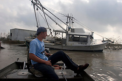 25 Sept, 2005. Cameron, Louisiana.  Hurricane Rita aftermath. <br /> Local man Aaron Stokes from nearby Carlyss surveys the damage at Hackberry on the way to hard hit Cameron. A shrimp boat lies awkwardly against a dock.<br /> Photo; &copy;Charlie Varley/varleypix.com