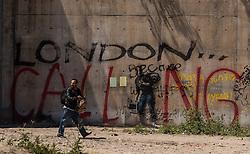 """24.06.2016, Dschungelcamp, Calais, FRA, der Dschungel von Calais, im Bild ein Migrant vor dem Schriftzug """"London is Calling"""". Das Camp ist eine provisorische Zeltstadt nahe der französischen Stadt Calais. Mehrere tausend Menschen kampieren dort in Zeltunterkünften und warten auf eine Möglichkeit zur illegalen Weiterreise durch den Eurotunnel nach Großbritannien. a migrant front the words """"London is Calling"""". The Calais Jungle is the nickname given to a migrant encampment, where migrants live while they attempt illegally to enter the United Kingdom at the Jungle Camp of Calais, France on 2016, 06, 24. EXPA Pictures © 2016, PhotoCredit: EXPA, JFK"""