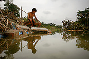 Mohammad Khokon sits next to what used to be his family's house. A flash flood washed it into the Jamuna River in Sirajganj, Bangladesh in 2007.<br /> Global warming cause the monsoon rain and floods to start earlier. Global warming also accellerate the melting of the ice and snow in the Himalayas, which feeds into the already saturated rivers that make the Ganges Delta. The result is devastating to people who live in the densely populated delta area.<br /> While the Himalayas and flooding wreak havoc from the north, rising sea levels cause salt water intrusion in the low-lying agricultural zones along the coast.<br /> According to the World Bank, coastal Bangladesh can easily see a 15 percent drop in rice production in the coastal regions within year 2050. The Khulna region is already damaged by salt water, but attempts are made to grow different strands of rice that can handle the stress.<br /> One of the poorest countries in the world, Bangladesh is also one of the most vulnerable to climate changes. With a sea level rise of 1.5 meter, close to 17 million people will be affected, according to GRID-Arendal, a knowledge center collaborating with UNEP.