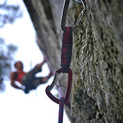 Climber silhouette against quickdraw.
