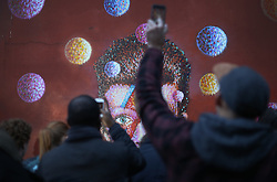 © Licensed to London News Pictures. 11/01/2016. London, UK. People crowd round a mural of David Bowie in Brixton. The Death of David Bowie, who was born in Brixton, has been announced today.  Photo credit: Peter Macdiarmid/LNP