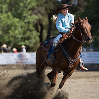 Dust flies as a barrel racing contestant comes to a near stop after competing in the event.