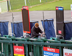 A bookmaker prepares his stand at Kempton Park Racecourse, Esher.