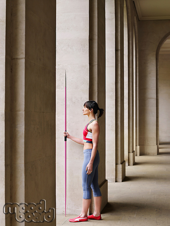Female athlete holding javelin standing in portico side view