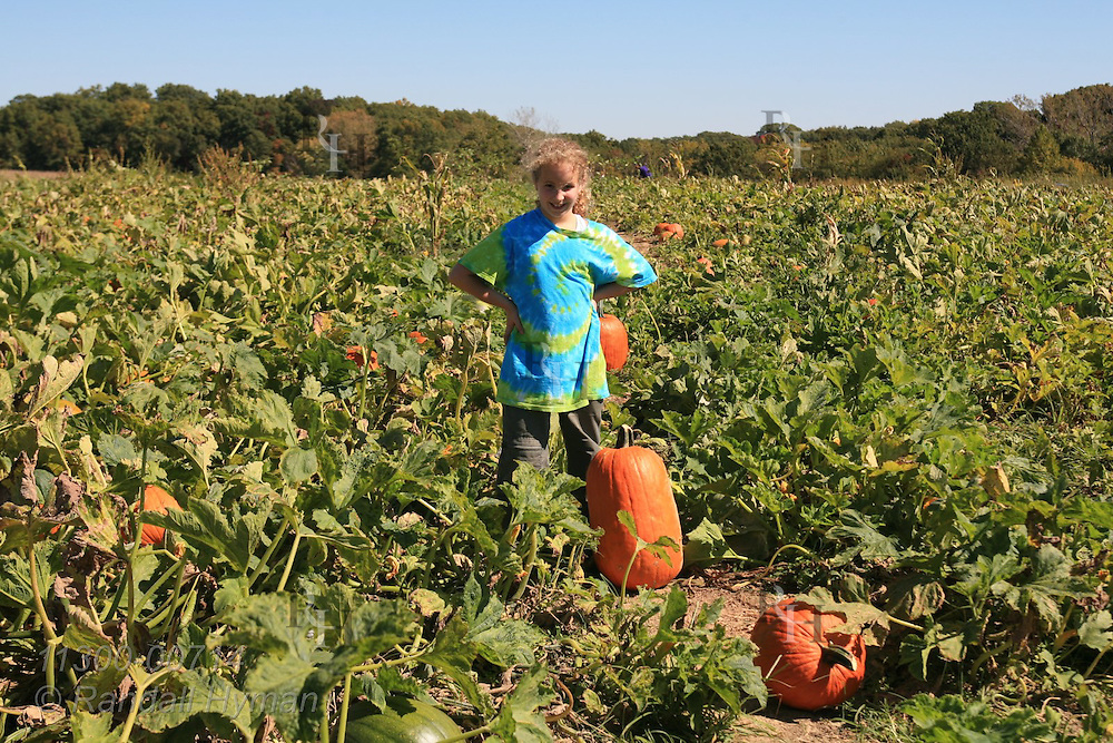 Nine-year-old girl finds perfect pumpkin in pick-your-own pumpkin patch at Eckert's farms near Grafton, Illinois.