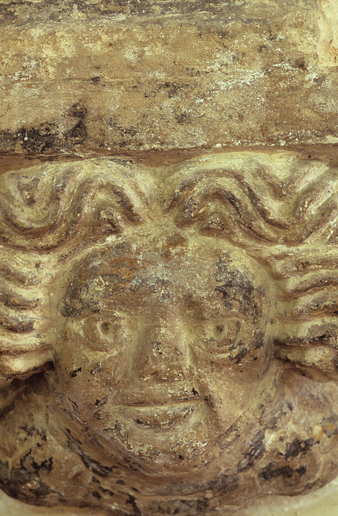 Naïve 16th century stone carving of face with wavy hair in church in Norfolk East Anglia England UK