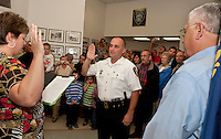 Gilford Town Clerk Denise Gonyer performs the swearing in ceremony for Gilford Police Chief Kevin Keenan Monday evening at Gilford Town Hall along with family and friends.    (Karen Bobotas/for the Laconia Daily Sun)