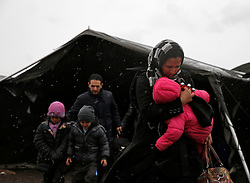 A migrant carries her baby as she makes their way to a tent where aid is distributed as migrants and refugees wait to continue their train journey to western Europe at a refugee transit camp in Slavonski Brod, Croatia, February 10, 2016. REUTERS/Darrin Zammit Lupi MALTA OUT. NO COMMERCIAL OR EDITORIAL SALES IN MALTA      TPX IMAGES OF THE DAY - RTX26C0P
