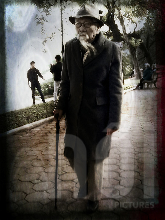 Elderly gentleman with a long white beard walks with a cane along the lakeside, Hanoi, Vietnam, Southeast Asia