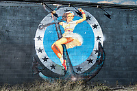 Anchor Girl artwork on a black cinderblock wall in the River Arts District in Asheville.