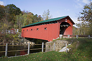 Red covered bridge over river.