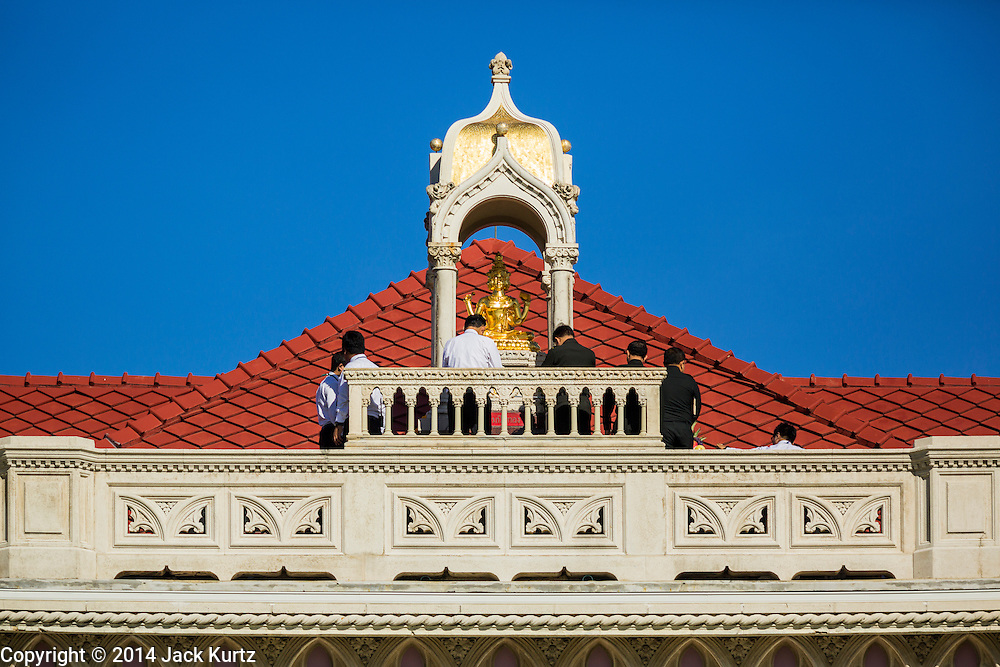 09 SEPTEMBER 2014 - BANGKOK, THAILAND:  Government officials make merit by praying at a Buddhist statue on the roof of Government House, the office of the Thai Prime Minister in Bangkok. Thai Prime Minister General Prayuth Chan-ocha named a cabinet that was dominated by members of the security forces to govern Thailand through at least a year of political reforms before elections are held. Prayuth and the cabinet met for the first time Tuesday. Before the meeting Prayuth said a prayer at a Buddhist shrine on the grounds of Government House, which is the Prime Minister's office. Prayuth seized power in a military coup in May. He was unanimously selected as Prime Minister by the National Legislative Assembly (NLA), the acting parliamentary body. Prayuth and his aides personally selected the members of the NLA after they seized power.      PHOTO BY JACK KURTZ