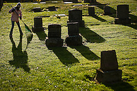 JEROME A. POLLOS/Press ..Alisa Ricciardi, 11, rakes between the rows of headstones Friday at the Forest Cemetery during a community service project. Students from the Coeur d'Alene Charter Academy took part in a historical tour of the cemetery and took part in a clean-up effort raking leaves and pine needles.