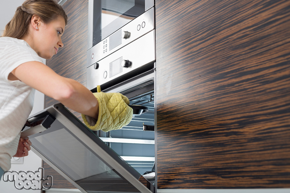 Woman placing dish in oven