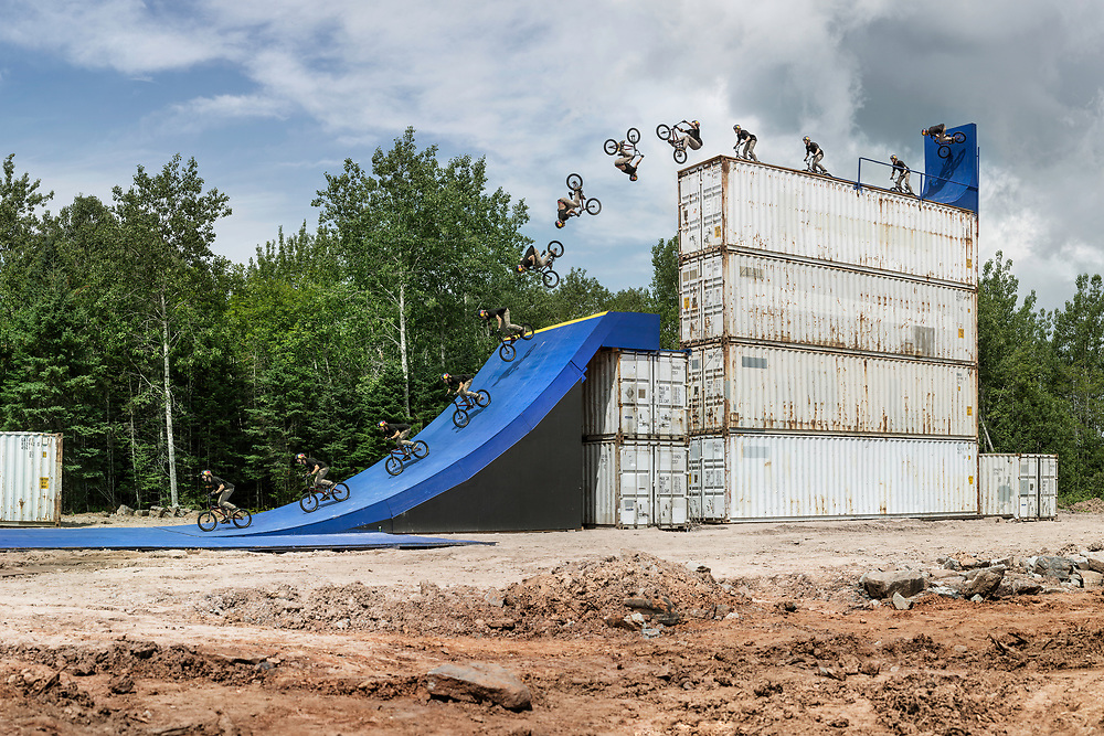 Drew Bezansen had a dream. He wanted to build a huge BMX park at the back of his friends property in his hometown of Truro, Nova Scotia using only wood and shipping containers. They first started by clearing trees and levelling the dirt. It took months to prepare and build all the features because it rained so hard everyday that the mud created made it impossible to move material around. Finally, we got our shooting window which was only a couple hours each day during a week in August, but only after the morning showers let up and just before the evening rain started again. We plugged away slowly that week creating more and more shots, saving this flat drop, the biggest of the entire set up, till the very last day. He had a few tricks in mind he was going to do but hadn't made up his mind about doing a backflip yet. The consequences were high and nothing of this size with a flat take off had ever been flipped before. Something in his head triggered and he yelled lets do it before being lifted on top by a crane. I was ready, shaking a bit, knowing I was only getting one chance for the shot, land or slam. My favourite part of the shot is the expression on his face in the landing frames.