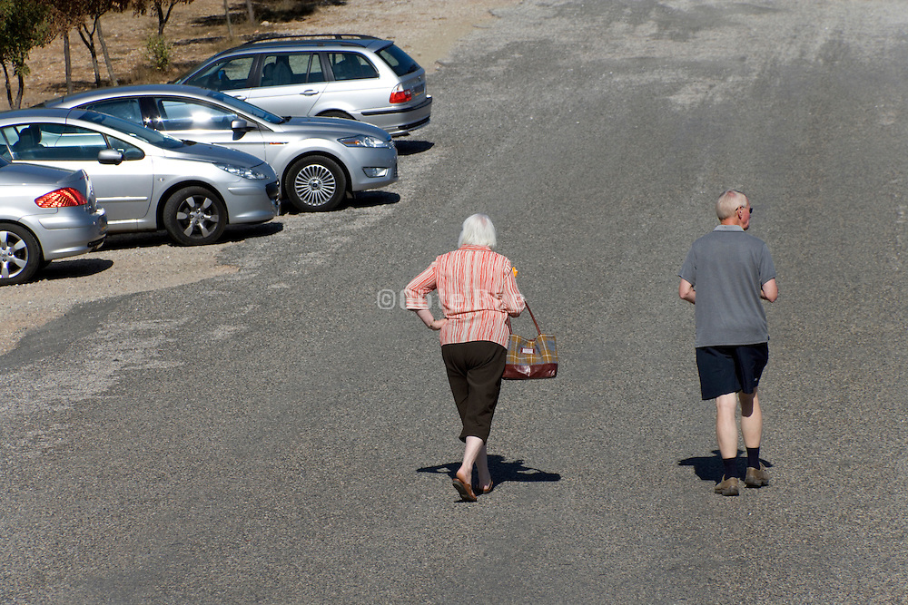 elderly couple walking to there car