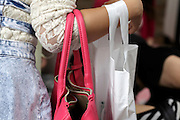 close up of young adult woman holding bags on her arm