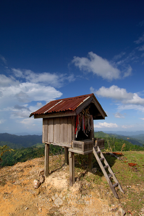 A Thai spirit house in Kanchanaburi, Thailand, against a mountain and jungle background with blue sky.