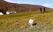 School canine Ketzel goes off path as teacher Corin Benedict, left, holds an advisor meeting with student Zoe Zelkha, right, as they walk through an upper field at the Mountain School