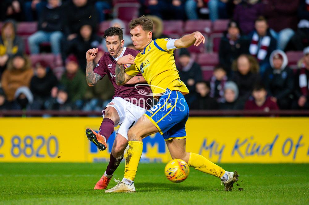 Jason Kerr (#15) of St Johnstone FC attempts to block a shot at goal from Jamie Walker (#10) of Heart of Midlothian FC during the Ladbrokes Scottish Premiership match between Heart of Midlothian FC and St Johnstone FC at Tynecastle Park, Edinburgh, Scotland on 14 December 2019.