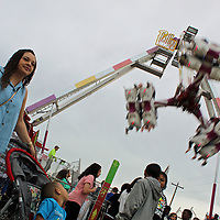 Holly Cunningham watches people at the carnival with her son, Leland, as the Flatline 360 runs in the background.