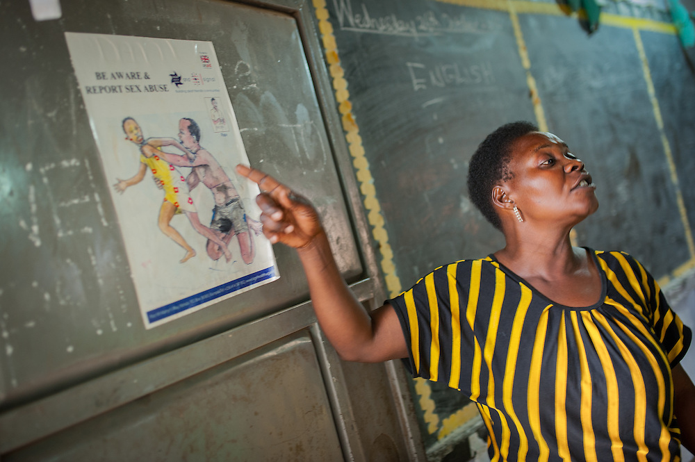 CAPTION: Alice Ajoi is SignHealth Uganda's 'focus teacher' at St Jude's Primary School. She has received special training in how to work with children who have a hearing impairment, which she uses in her own classroom and also teaches to other staff. Outside of school, she also works among the wider community in Lukaya, providing support to parents and helping to increase awareness. Here, we see her teaching children about sexual abuse, which is sadly far more common among children with hearing impairment because they are often already ostracised and easy to target as 'silent victims'. LOCATION: St Jude's Primary School, Lukaya Town, Kalungu District, Central Region, Uganda. INDIVIDUAL(S) PHOTOGRAPHED: Alice Ajoi.