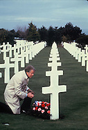 President Jimmy Carter lays a wreath in the cemetery in Normandy, France  January 1, 1978<br /> Photo by Dennis Brack<br /> <br /> <br /> A photographers note.  This picture portrays a peaceful reflective, quiet scene.  It should have been but  at this moment the White House press pool and the French pool were engaged in a major battle.  Lots of pushing swearing and shoving with photographers on the ground.  The White House had prepositioned the White House pool and then the French pool was let in.  The French would have none of this and the fight began.  Carter knew the fight was going on.  How could he not know when you have about 12 grown men fighting three feet  from you.  Carter just laid the wreath, and went on to the motorcade.