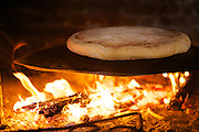 A Turkish flat bread being baked on an open fire.
