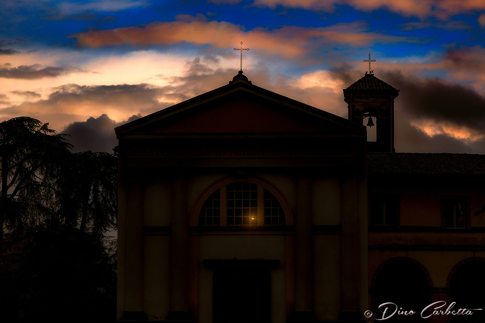 """""""The sun sets behind the Church of San Giacomo Maggiore - Orvieto""""...<br /> <br /> Orvieto is one of the most striking, memorable, and enjoyable hill towns in central Italy. Less than 90 minutes from Rome, Orvieto sits majestically high above the valley floor atop a big chunk of volcanic stone called tufa, and overlooking cypress-dotted Umbrian plains and vineyards. The ancient city rewards one with a peaceful and historical stroll back in time to the days of the Etruscans, who built this cliff top village over 2000 years ago for protection from their enemies. The ancient Etruscan wall still stands today presenting colorful cliffside views, and protecting the famous Duomo di Orvieto, the Palazzo del Popolo, and other antique treasures. A hospice for the poor and traveling pilgrims was established on this location in 1187 and the site eventually developed into a civic hospital.  Pope Clement IV gave permission for the erection of a chapel and cemetery in 1266.  Eventually the church finally closed in 2000, when the new Ospedale di Santa  Maria della Stella opened at nearby Ciconia."""
