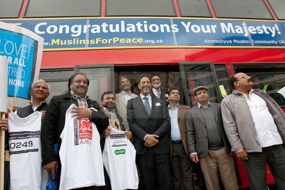 "© licensed to London News Pictures. London, UK 10/05/2012. Muslim supporters of Diamond Jubilee posing next to a bus with has a banner reading ""Congratulations Your Majesty!"" outside Tower of London, today (10/05/12). Ahmadiyya Muslim Association and various charities launching a campaign to celebrate the Queen's Diamond Jubilee. The campaign will have 100 London buses with banners reading ""Congratulations Your Majesty!"" and a charity walk on this Sunday. Photo credit: Tolga Akmen/LNP"