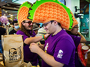 24 JANUARY 2019 - BANGKOK, THAILAND:  Americans, wearing giant foam tacos, with their orders at the first Taco Bell in Thailand, which opened Thursday. The restaurant has a 215 square meter space in the Mercury Ville, a mixed use retail/office building in central Bangkok. Taco Bell is owned by Yum Brands, which also owns KFC, Pizza Hut, and WingStreet. Taco Bell in Thailand joins KFC, which has more than 500 restaurants in Thailand and Pizza Hut, which recently started expanding in Thailand.     PHOTO BY JACK KURTZ