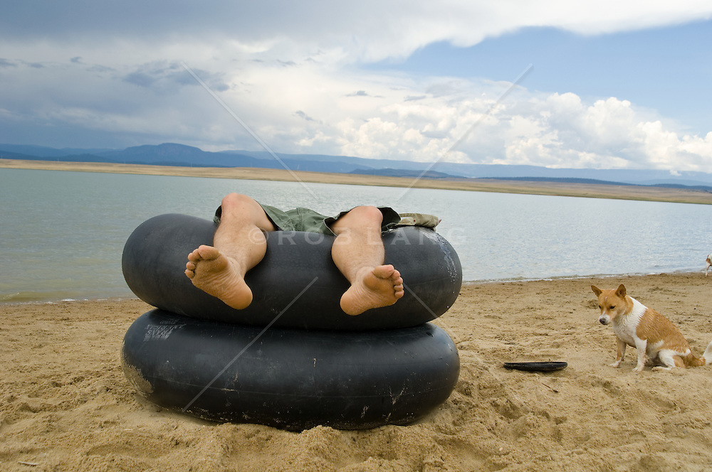 man in an inner tube on the shore of a lake and a dog waiting to play fetch with a stick.