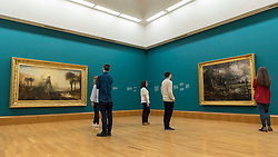 "© Licensed to London News Pictures. 25/05/2018. LONDON, UK. Staff members view works at the preview of Fire and Water, a display of masterpieces by Constable and Turner at Tate Britain.  On display for the first time in 180 years alongside each other are (L to R) ""Caligula's Palace and Bridge"", 1831, by J.M.W. Turner and ""Salisbury Cathedral from the Meadow"", 1831, by John Constable.  The works will on display 26 May 208 to July 2019.  Photo credit: Stephen Chung/LNP"