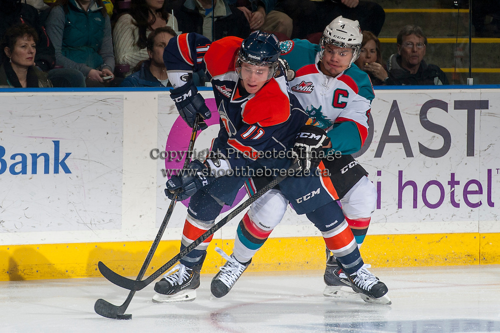 KELOWNA, CANADA - DECEMBER 27: Madison Bowey #4 of the Kelowna Rockets checks Aspen Sterzer C #11 of the Kamloops Blazers during the first period on December 27, 2013 at Prospera Place in Kelowna, British Columbia, Canada.   (Photo by Marissa Baecker/Shoot the Breeze)  ***  Local Caption  ***