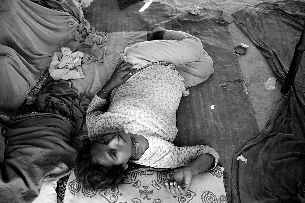 Hamida, 36 weeks and 6 days pregnant anxiously awaits the birth of her 4th baby. Conditions in the tent camp are not ideal for pregnant women and most suffer from high blood pressure and lack of vitamins. Karachi, Pakistan, 2010