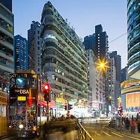 China, Hong Kong, Hong Kong Tramways street cars stopped at traffic light in city center under glowing street lights at dusk on winter evening