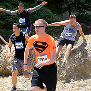 Competitors in action at the straw bale obstacle during the Reebok Spartan Race. Mohegan Sun, Uncasville, Connecticut, USA. 28th June 2014. Photo Tim Clayton