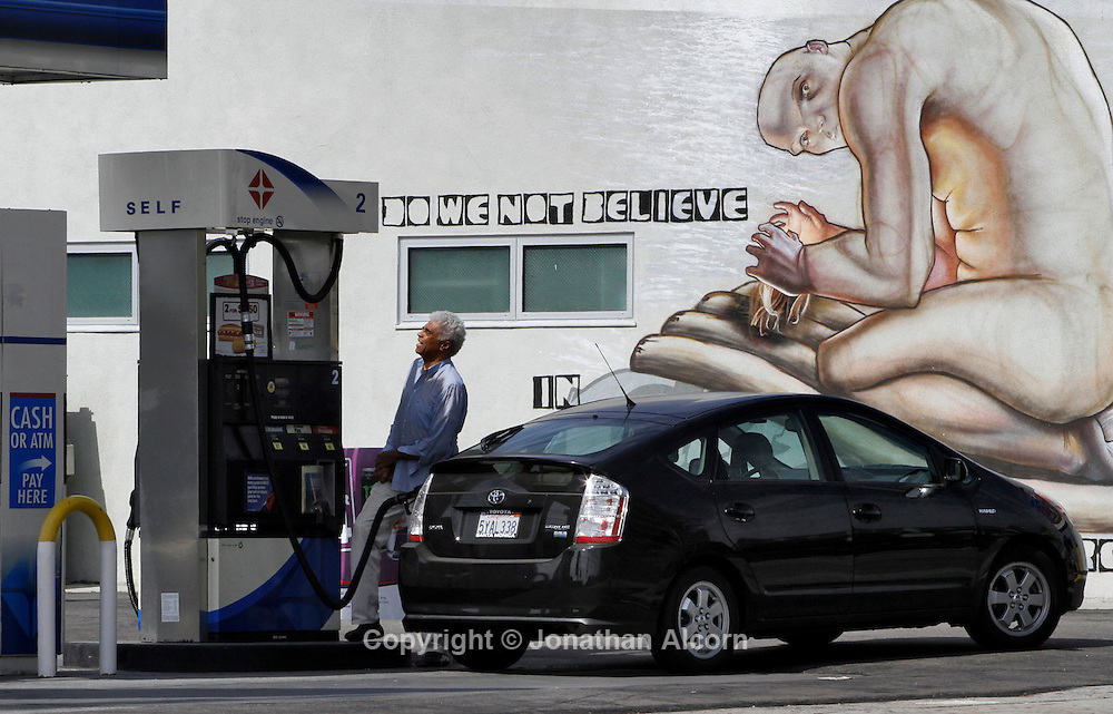 A man pumps gas into his Toyota Prius at a gas station in Los Angeles on the day the price of gasoline has hit an all-time average high in California of $4.6140 a gallon